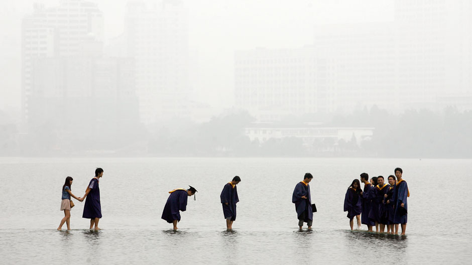 Students in graduation robes stand on a stone bridge submerged underwater at the flooded Donghu Lake in Wuhan, Hubei province, June 21, 2011