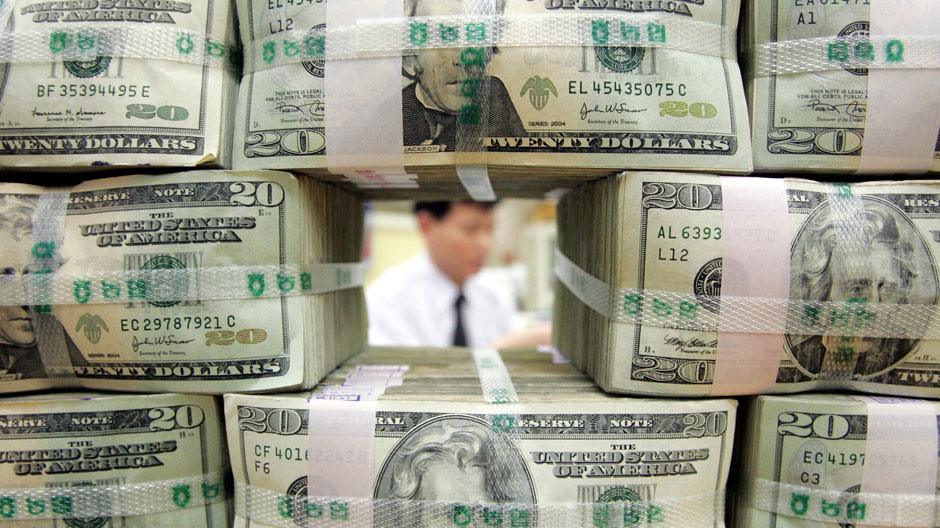 A bank clerk works behind twenty-dollar bills piled at a bank in Seoul November 9, 2004
