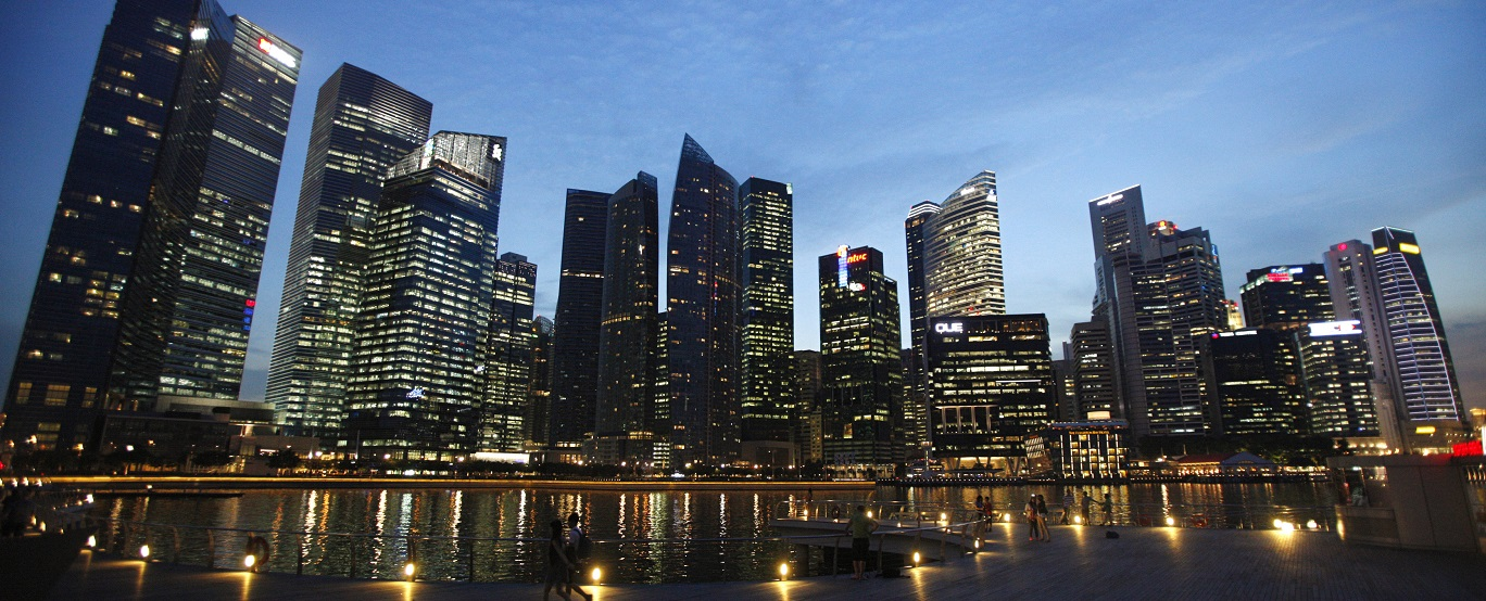 People walk past the skyline of Marina Bay central business district in Singapore